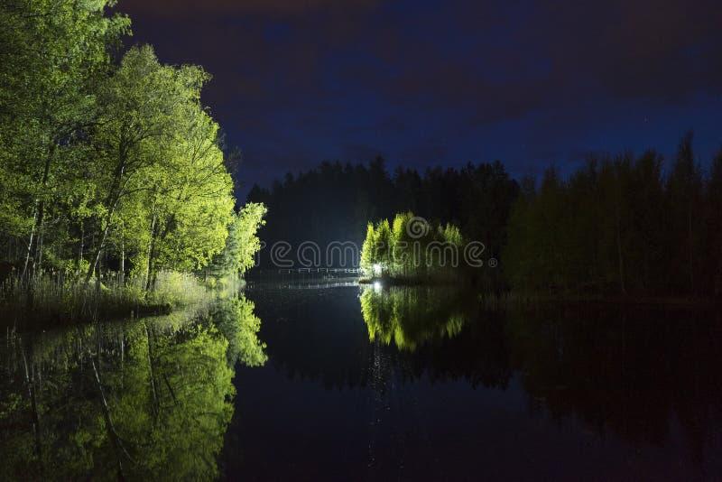 Mens die zich openlucht bij donkere nacht die met flitslicht glanzen bevinden royalty-vrije stock fotografie