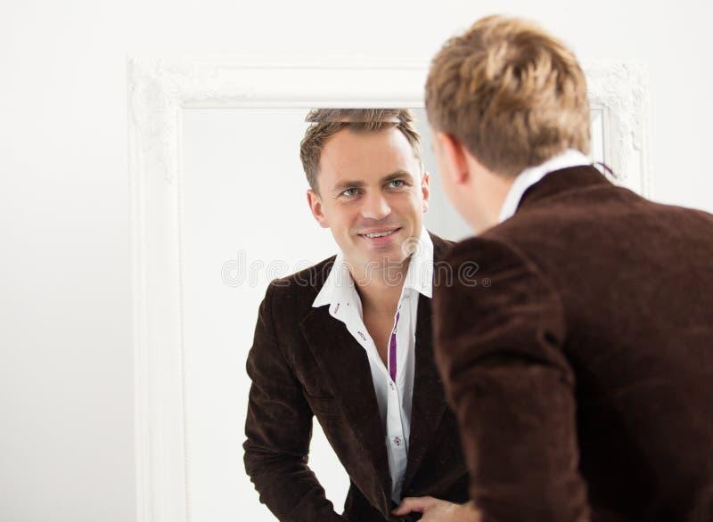 Mens die zich in spiegel bekijkt stock foto's