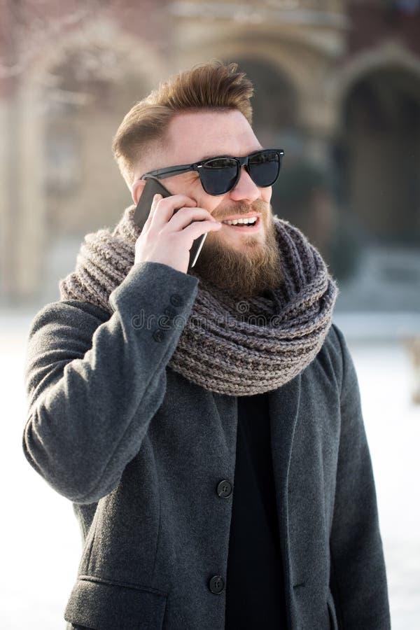 Mens die zich in stad tijdens de wintertijd bevinden en telefoonconvers hebben royalty-vrije stock fotografie