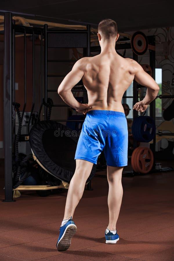 Mens die zich sterk in de gymnastiek en spieren buigen bevinden royalty-vrije stock foto's