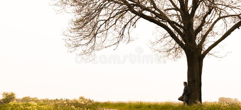 Mens die zich tegen een boom bevindt stock afbeelding