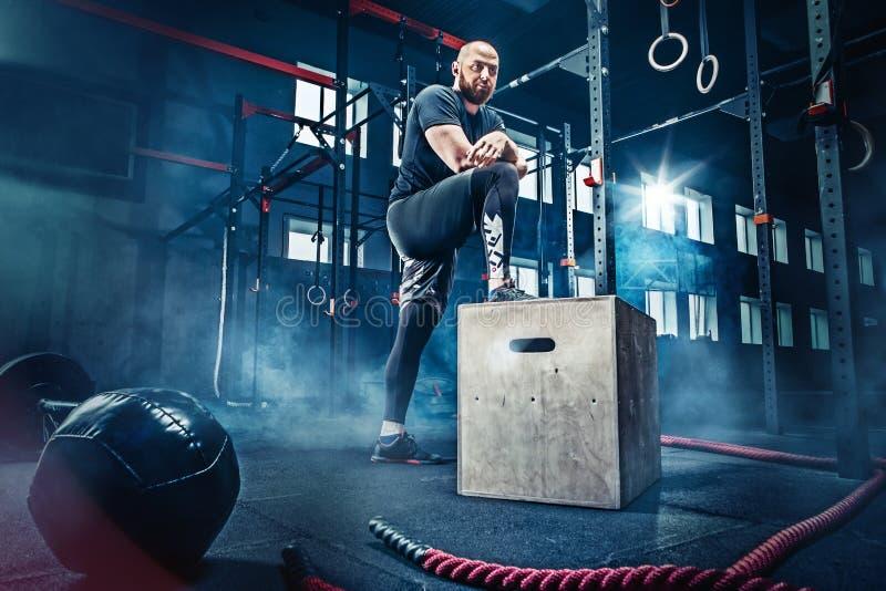 Mens die zich tijdens oefeningen in de geschiktheidsgymnastiek bevinden Crossfit stock fotografie
