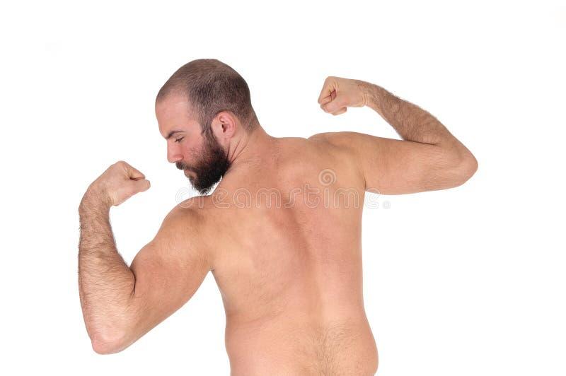 Mens die zich van achter shirtless bevinden tonend zijn spieren royalty-vrije stock afbeelding