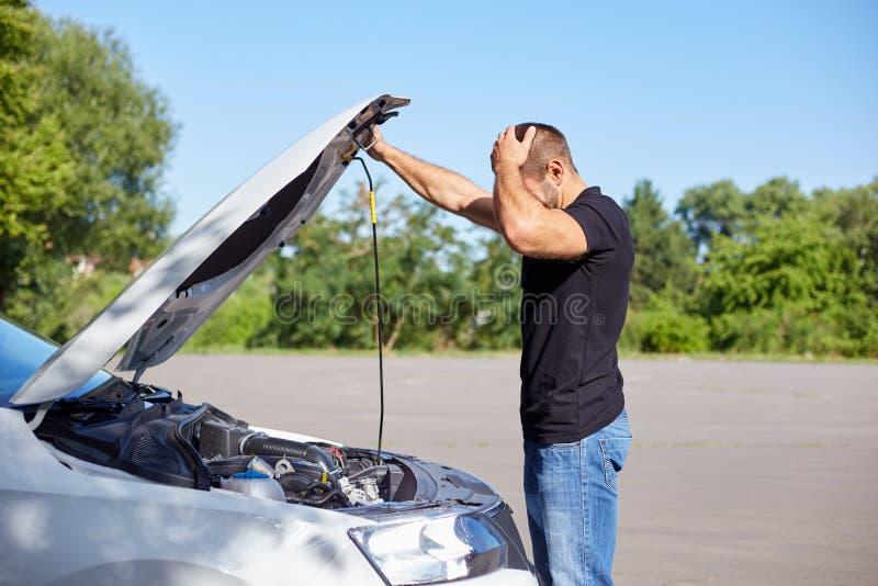 Mens die zich voor een gebroken auto bevinden stock fotografie