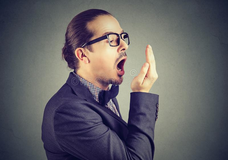 Mens die zijn adem met het gebaar van de handtest controleren stock afbeeldingen