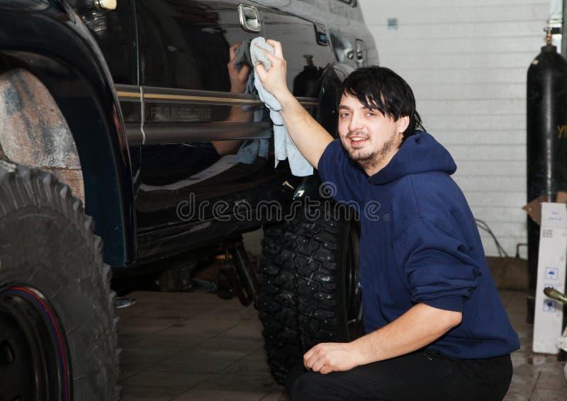 Mens die zijn auto in de garage wassen royalty-vrije stock afbeeldingen