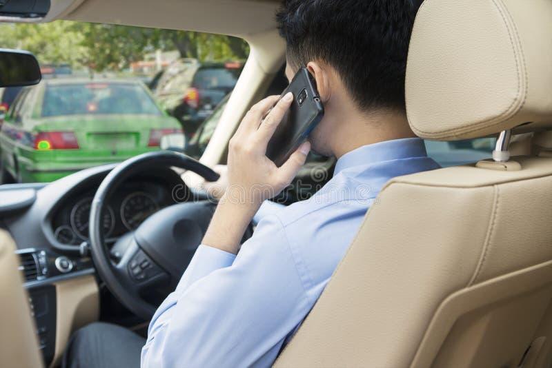 Mens die zijn auto drijven terwijl het spreken op de telefoon royalty-vrije stock afbeelding
