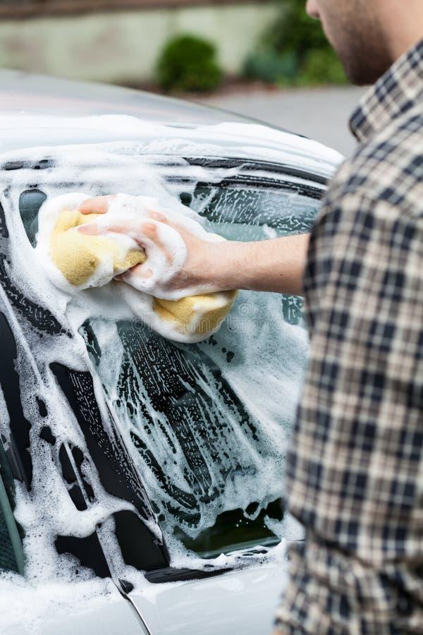 Mens die zijn auto schoonmaken royalty-vrije stock foto