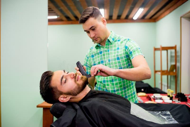 Mens die zijn baard in orde gemaakt krijgen royalty-vrije stock afbeelding