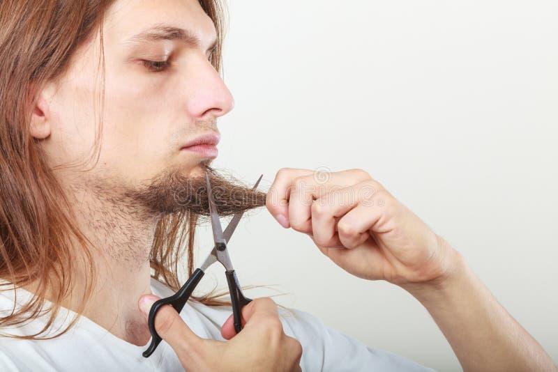 Mens die zijn baard snijden royalty-vrije stock afbeeldingen
