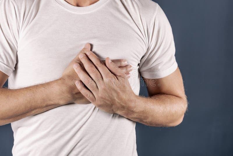 Mens die zijn borst met beide handen houden, die hartaanval of pijnlijke klemmen, die op borst met pijnlijke uitdrukking op blauw stock foto's