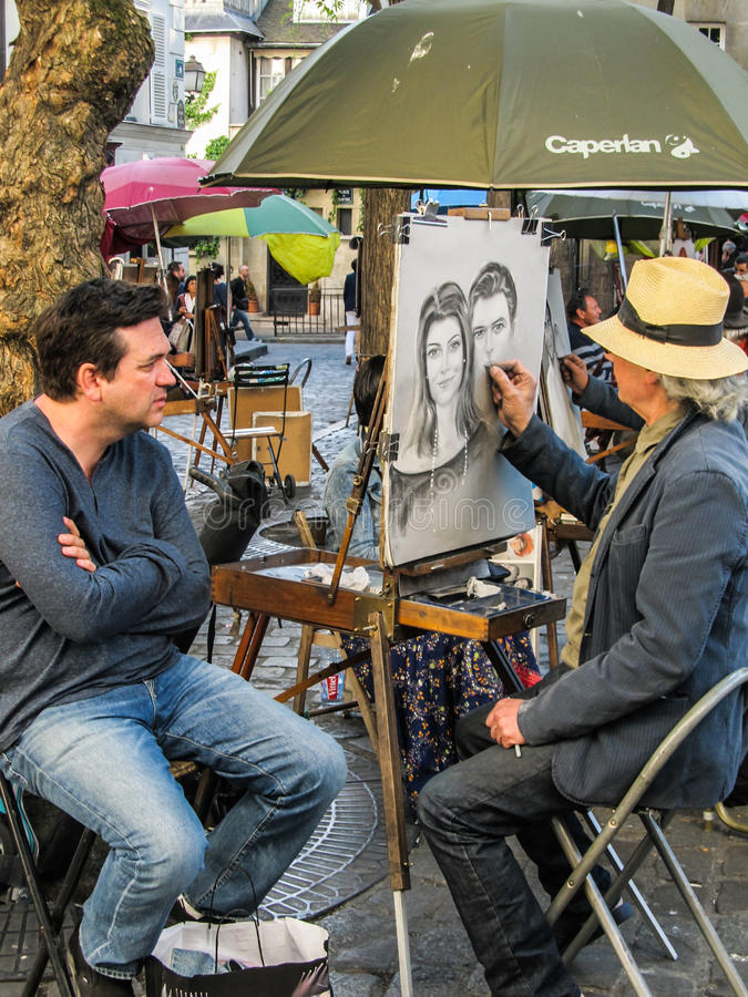 Mens die zijn die gezicht krijgen door straatkunstenaar wordt geschetst op de straten van Montmartre, Parijs royalty-vrije stock afbeelding