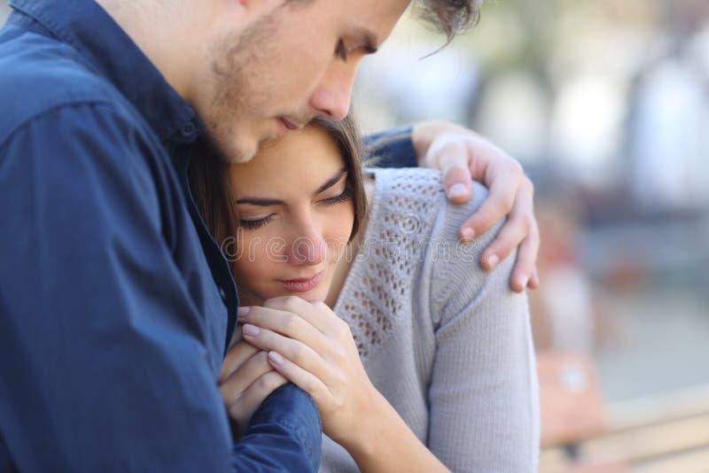Mens die zijn droevige rouwende vriend troosten stock afbeelding