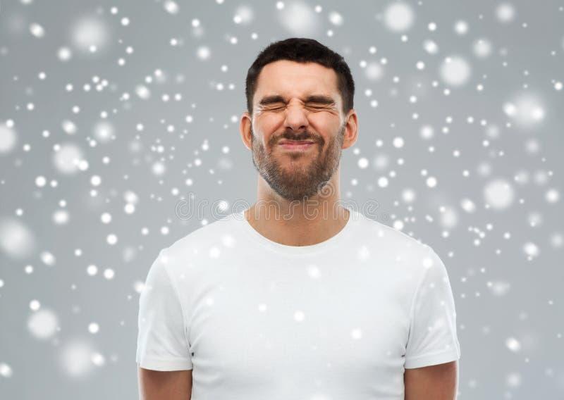Mens die zijn gezicht over sneeuwachtergrond verknoeien stock afbeeldingen