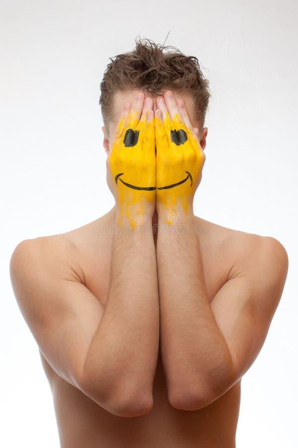 Mens die zijn gezicht verbergt onder glimlachmasker royalty-vrije stock afbeeldingen