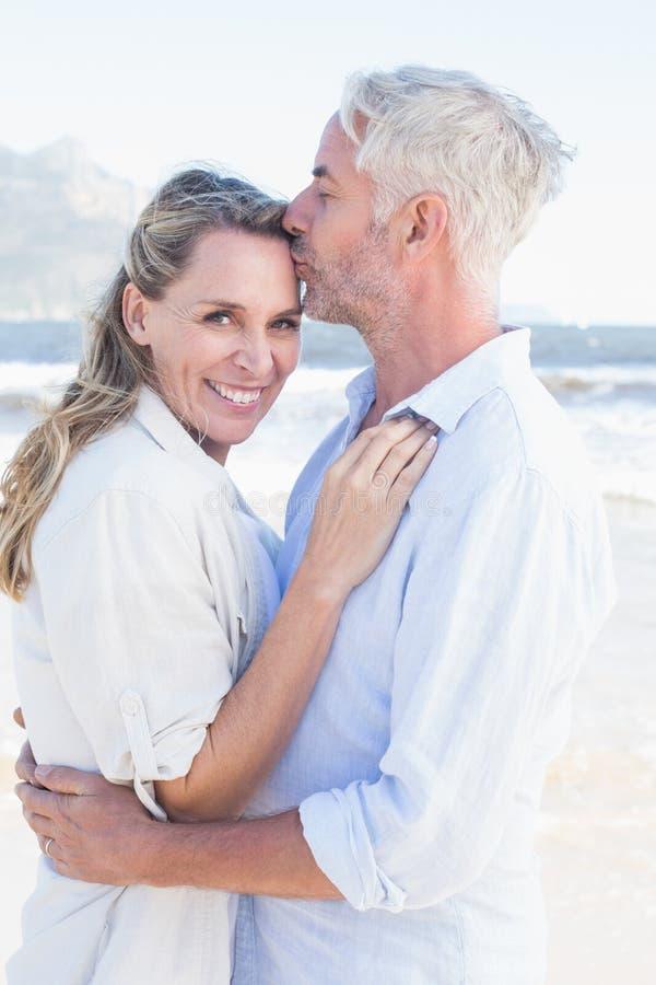 Mens die zijn glimlachende partner op het voorhoofd kussen bij het strand stock foto's