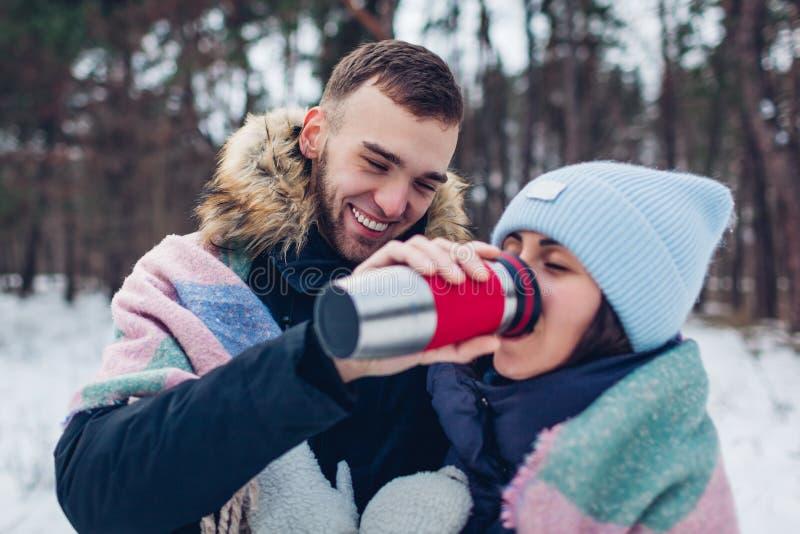 Mens die zijn meisje hete thee geven aan drank in thermosflessenkop Houdend van paar die in de winterbos samen lopen stock foto's