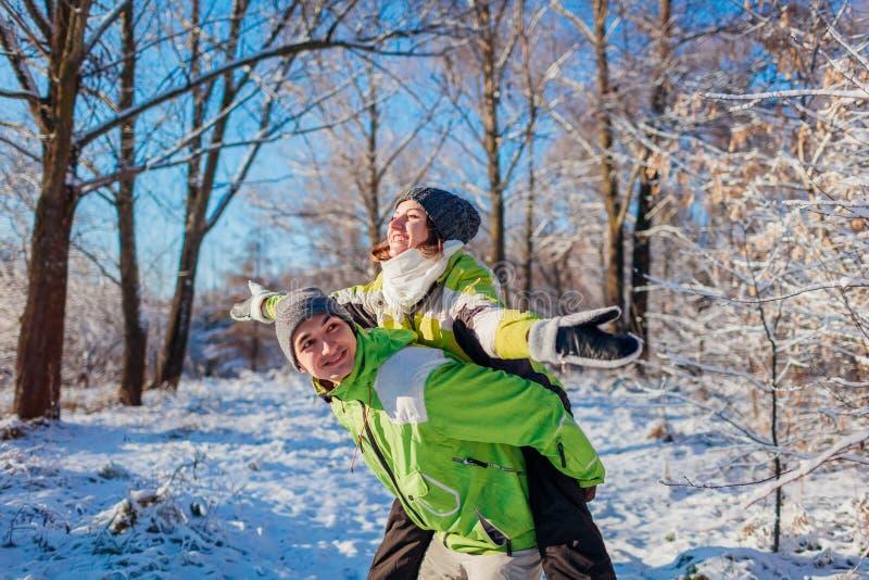Mens die zijn meisjevervoer per kangoeroewagen in de winter bospaar geven in liefde die pret hebben stock fotografie