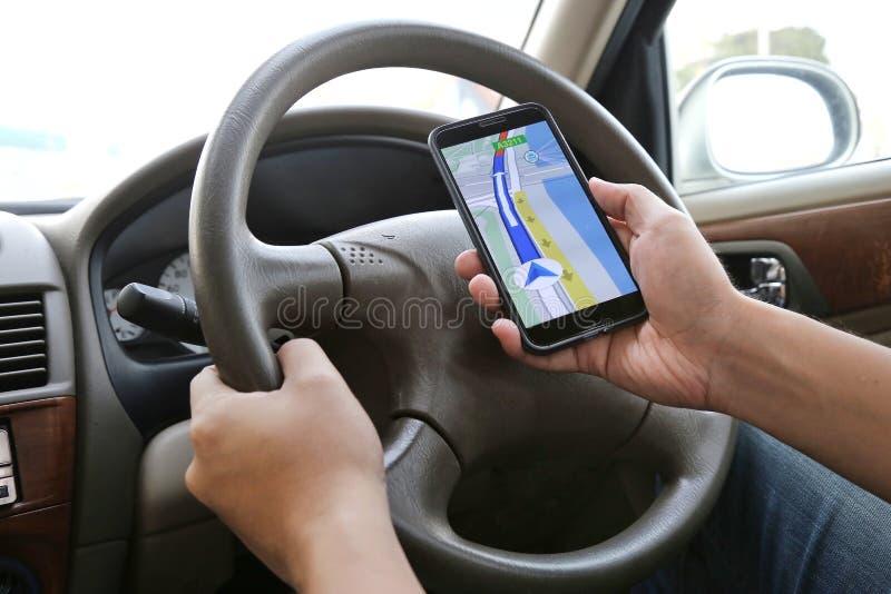 Mens die zijn mobiele telefoon met behulp van om met kaarttoepassing te navigeren terwijl het drijven Gevaarlijke bestuurder o stock afbeeldingen