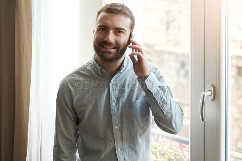 Mens die zijn mobiele telefoon thuis met behulp van royalty-vrije stock afbeelding