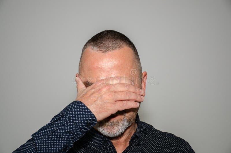 Mens die zijn ogen behandelen met één hand stock afbeelding