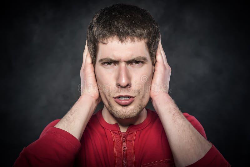 Mens die zijn oren behandelt royalty-vrije stock afbeelding