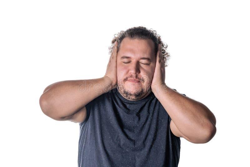 Mens die zijn oren witn handen behandelen, die zijn die ogen sluiten, op witte achtergrond worden geïsoleerd Hoor geen kwaad conc stock fotografie