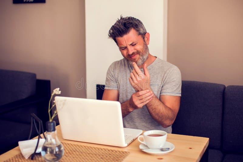 Mens die zijn polspijn van het gebruiken van computer houden De handpijn van het bureausyndroom door beroepsziekte royalty-vrije stock afbeelding