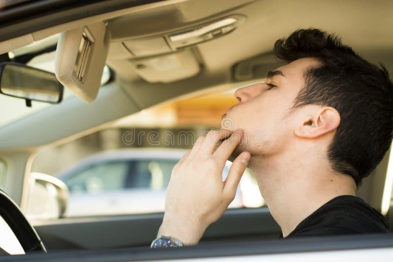 Mens die zijn Pukkel bekijken die Spiegel van een Auto gebruiken royalty-vrije stock afbeelding
