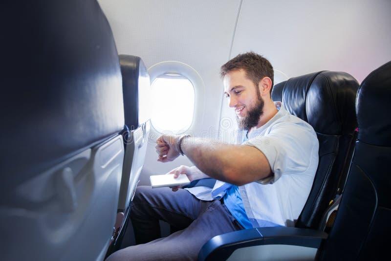 Mens die zijn slim horloge in vliegtuig bekijken stock foto