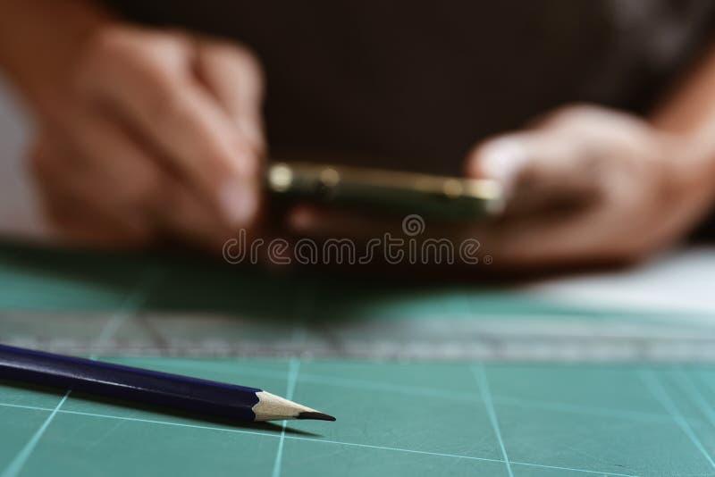 Mens die zijn smartphone gebruiken op het zijn werk stock foto