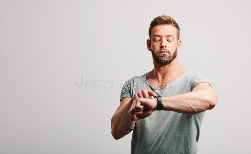 Mens die zijn smartwatch controleren stock fotografie