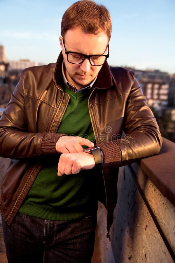 Mens die zijn smartwatchtouchscreen gebruiken die zich op het dak bevinden stock afbeelding