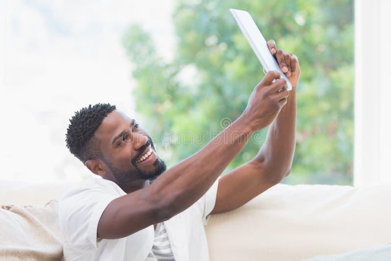 Mens die zijn tablet op te nemen laag gebruiken selfie royalty-vrije stock afbeelding