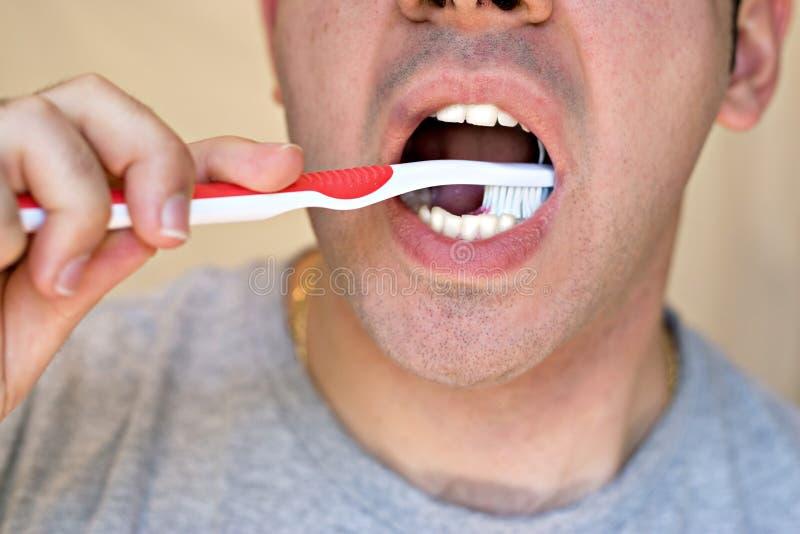 Mens die Zijn Tanden borstelt stock afbeelding