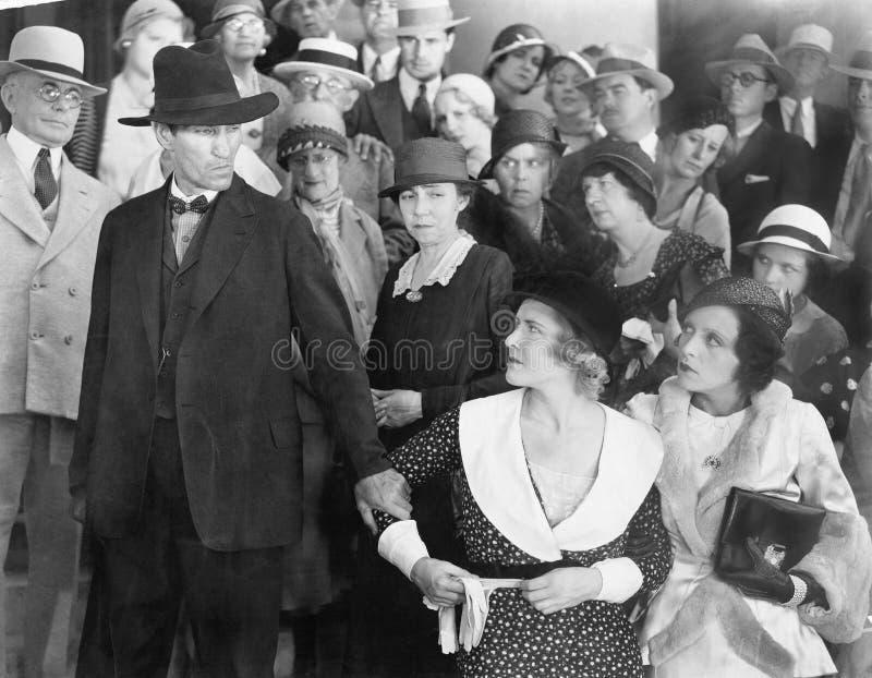 Mens die zijn vrouw in woede bekijken terwijl een groep mensen let op (Alle afgeschilderde personen langer ex leven niet en geen  stock afbeeldingen