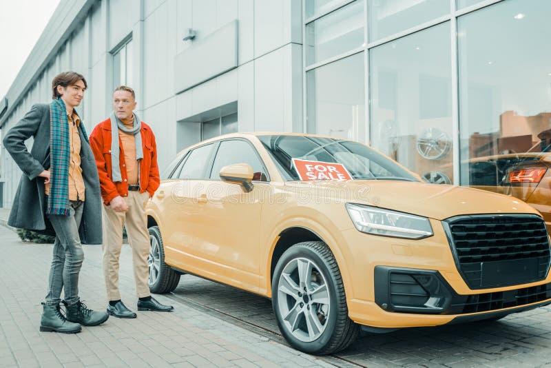 Mens die zijn zoon een nieuwe auto kopen royalty-vrije stock afbeelding