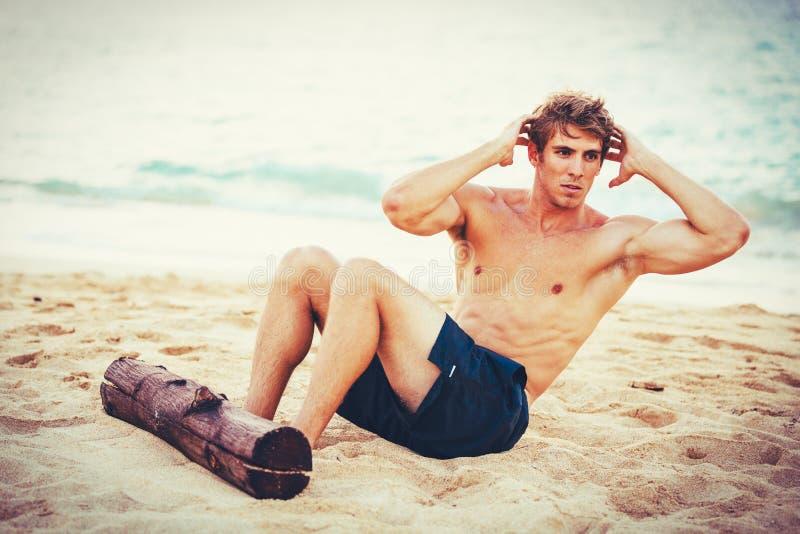 Mens die zitten-UPS in openlucht op het Strand doen royalty-vrije stock foto's