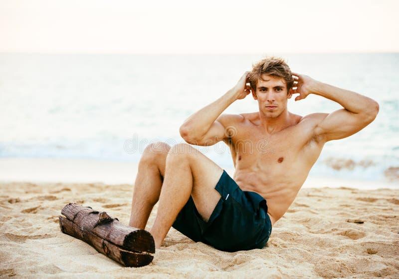 Mens die zitten-UPS in openlucht op het Strand doen royalty-vrije stock afbeelding