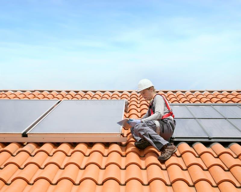Mens die zonnepanelen installeren op dak stock foto's