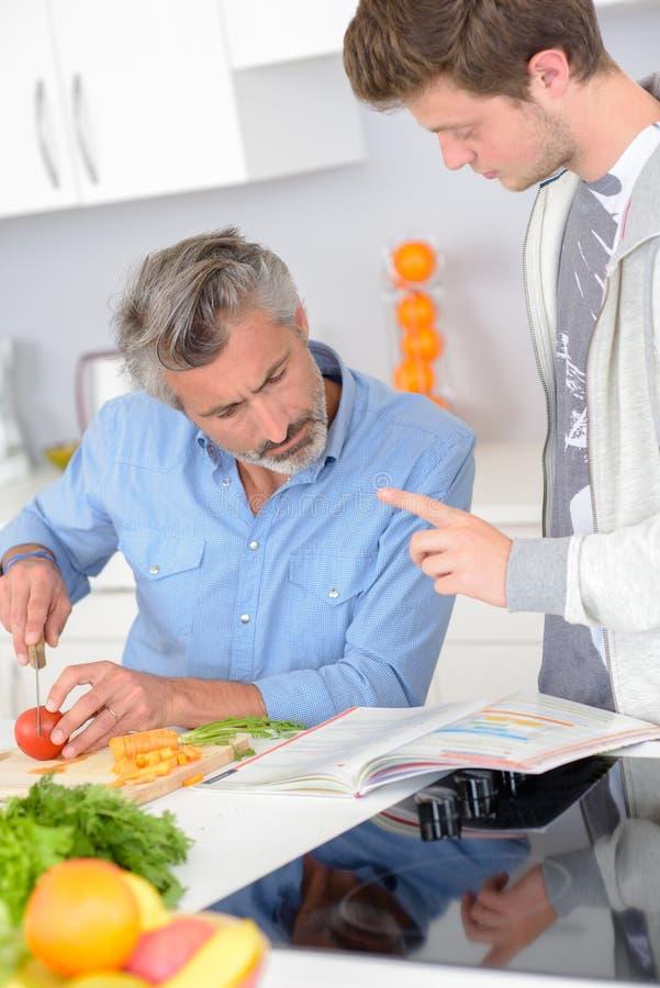 Mens die zoons` s handboek bekijken terwijl het voorbereiden van maaltijd stock foto