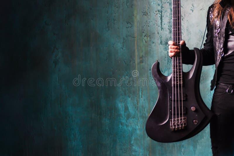Mens die in zwart leer een gitaar houden Tuimelschakelaar en metalhead, de jeugdstijl, muziek Geweven achtergrond, plaats voor te royalty-vrije stock fotografie