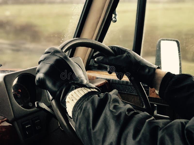 Mens die zwarte leer drijfhandschoenen in uitstekend voertuig dragen stock foto's