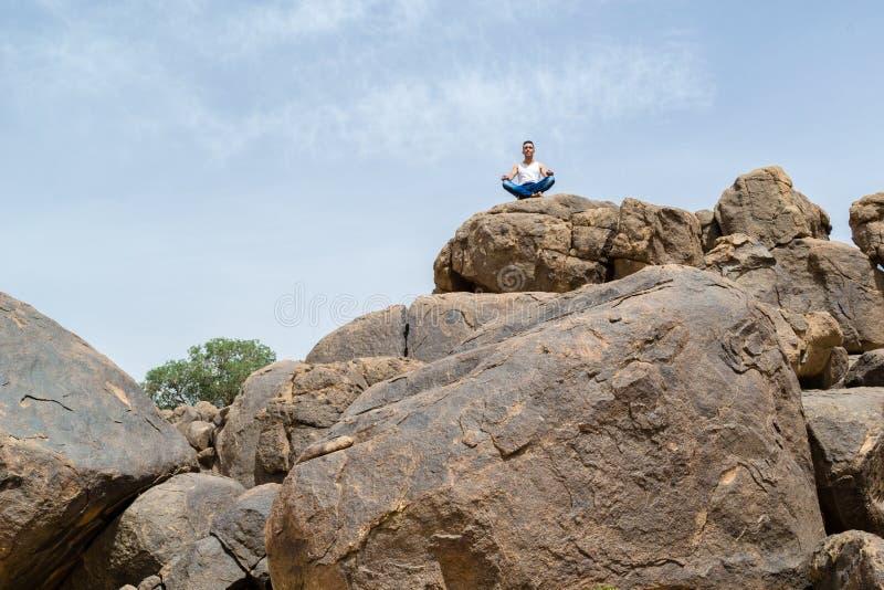Mens in diepe yogaconcentratie op een rotsachtige berg - landschap stock afbeelding
