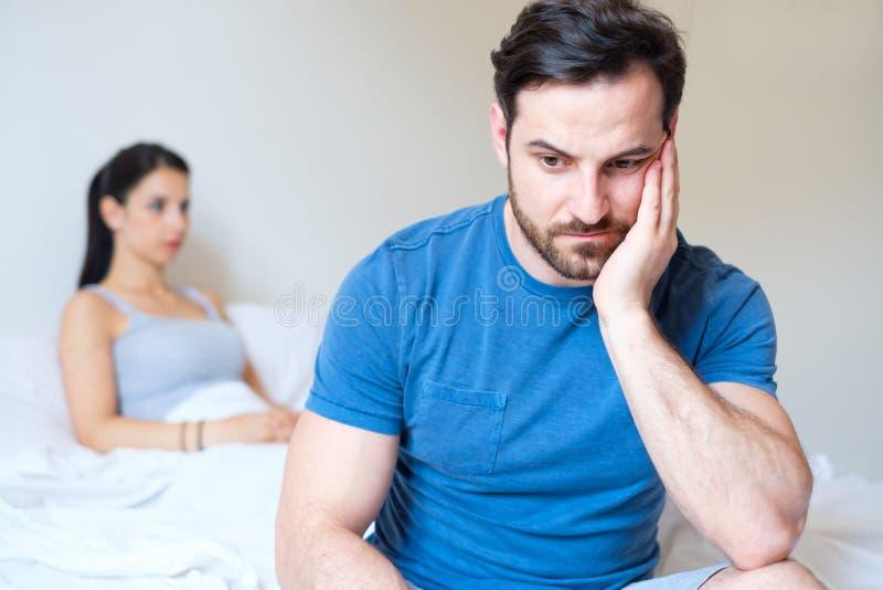 Mens droevig na het debatteren met zijn meisje in het bed royalty-vrije stock afbeeldingen