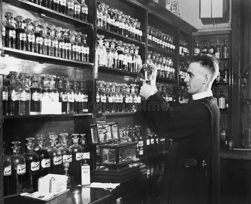 Mens in een apotheek die geneeskunde mengen (Alle afgeschilderde personen leven niet langer en geen landgoed bestaat Leveranciers stock foto's