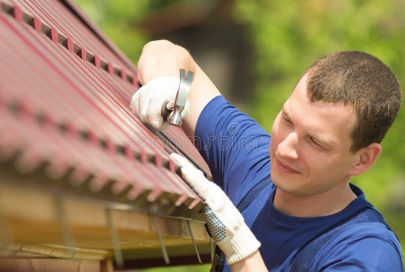 Mens in een blauw kostuum die het dak van het huis, close-up herstellen royalty-vrije stock afbeelding
