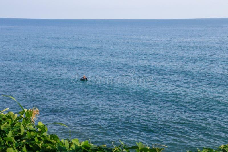 Mens in een boot bij blauwe overzees stock fotografie