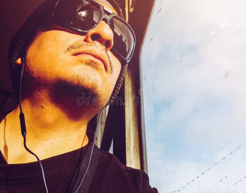 Mens in een bus Knappe jonge Peruviaanse mens die zonnebril dragen die door busvenster kijken royalty-vrije stock foto's