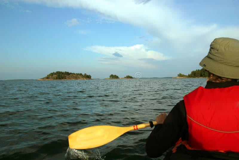 Mens in een kajak die naar een eiland, Scandinavië paddelen royalty-vrije stock afbeeldingen